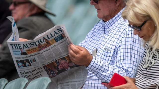 Man reads newspaper next to woman on phone
