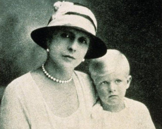 Princess Alice holds her toddler Prince Philip on her lap in a black and white portrait picture