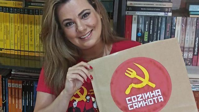 Marcelle Nogueira Toscani segura embalagem de papel com o logotipo de sua marmitaria vegana Cozinha Canhota, que contém a imagem de um garfo e foice, com o garfo no lugar do martelo do símbolo do comunismo
