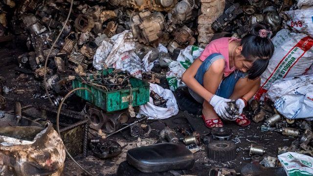 Adolescente reciclando componentes de bateria e outros resíduos eletrônicos no Vietnã