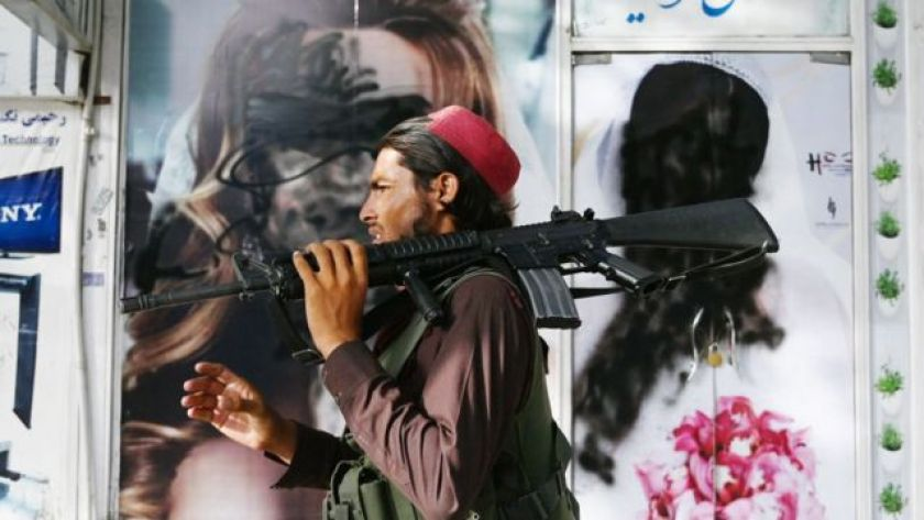 A Taliban fighter walks past a beauty salon carrying an M16 weapon.