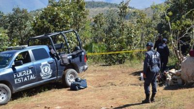 Mexican Federal Police officers work at the site where 20 clandestine tombs were found, in the municipality of Zitlala, Guerrero State, Mexico, 24 November 2016.