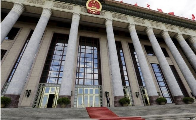 """An officer stands outside the Great Hall of the People, the venue of National People""""s Congress, China""""s parliament, in Beijing, June 18, 2015."""