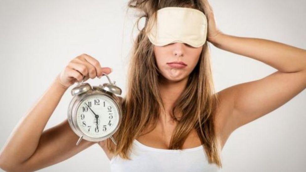 yeni uyanan bir kadın elinde saat tutuyor