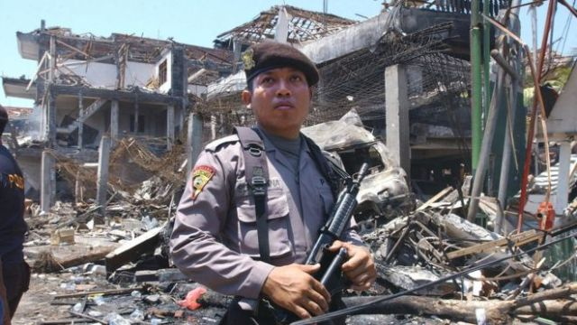 An armed Indonesian policeman guards what remains of a nightclub in the aftermath of the Bali bombing in October 2002.