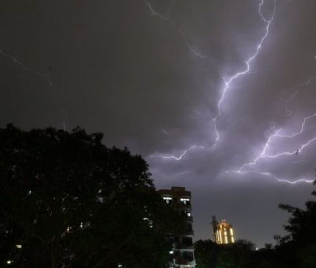 Lightning Strikes Over Residential Apartments During A Thunderstorm On The Outskirts Of The Indian Capital New