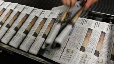 A rack of newspapers on top of one another