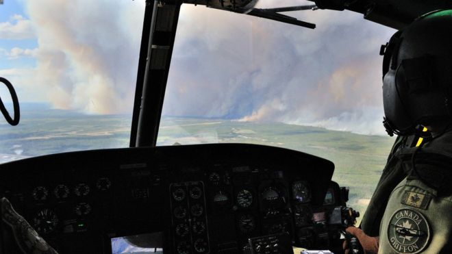 Members of the 408 Tactical Helicopter Squadron, Edmonton fly a CH-146 Griffon to view the damage created by wild fires in the Fort McMurray (07 May 2016)