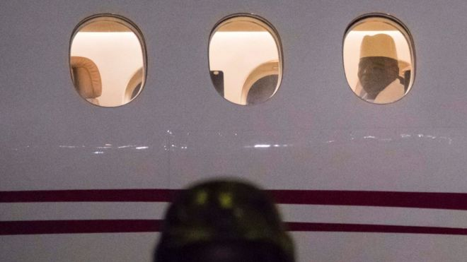 Former president Yaya Jammeh the Gambia's leader for 22 years, looks through the window from the plane as he leaves the country on 21 January 2017 in Banjul airpor
