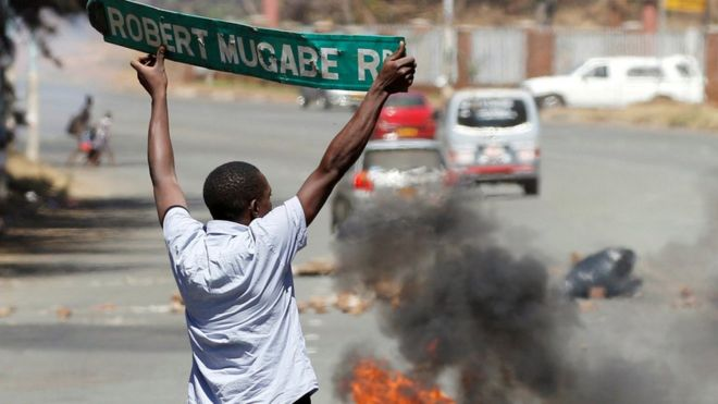 man holds sign for Robert Mugabe Rd that has been taken down