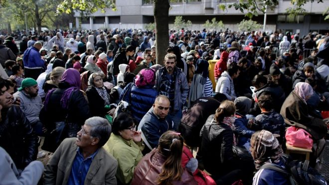 In this file photo taken Wednesday, 30 September 2015, hundreds of migrants and refugees wait for Berlin's State Office of Health and Welfare, the cities central registration point for asylum seekers in Berlin, Germany.