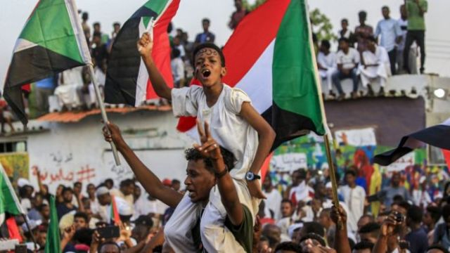 A boy carrying a Sudanese flag sits on a man's shoulders, amid a celebrating crowd