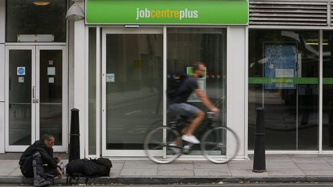 A cyclist passes the entrance to a job centre in east London