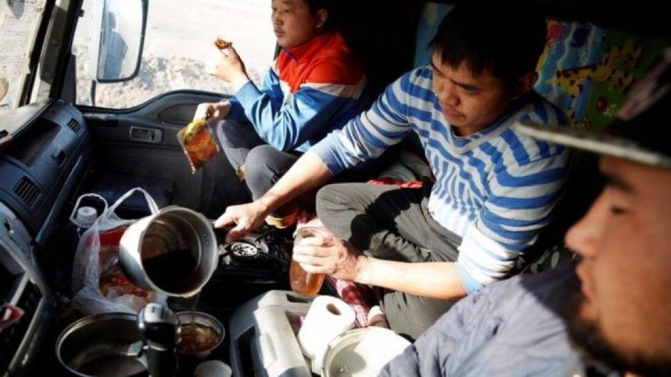 Camioneros de Mongolia cocinan y comen arriba del camión.