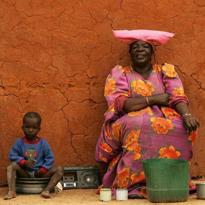 Mulher herero em frenta a uma casa, ao lado de um menino