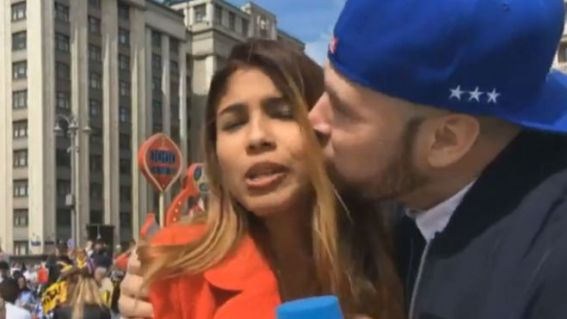 A female reporter is kissed, by a fan, clearly looking uncomfortable, holding a DW mic