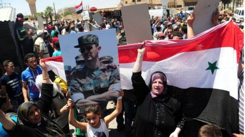 Dera'da Beşar Esad fotoğrafı ve Suriye bayrağı taşıyan kadın ve çocuklar