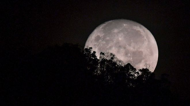 The moon sets behind trees on a hill before sunrise in Karak, in the suburbs of Pahang outside Kuala Lumpur,
