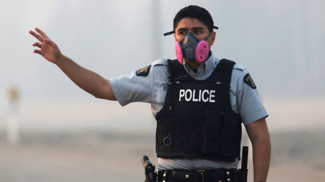 A police officer wears a mask to protect himself from smoke from the wildfires as he directs traffic near Fort McMurray (07 May 2016)