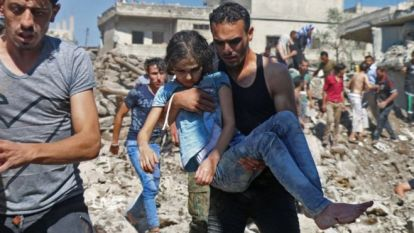A man carries a girl rescued from a building hit in a suspected government air strike in the rebel-held town of Nawa, north of Deraa, Syria (26 June 2018)