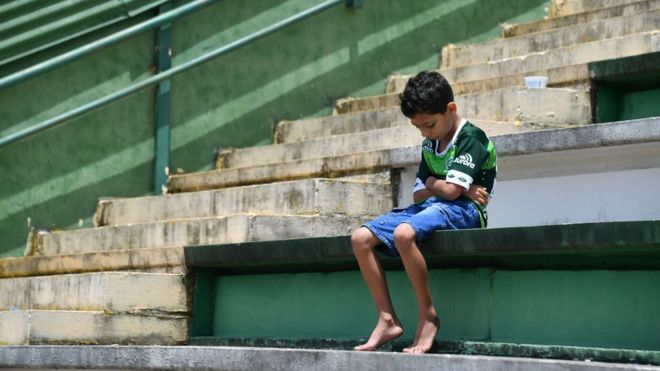 A boy sits alone on the stands during a tribute to the players of Brazilian team Chapecoense Real who were killed in a plane accident in the Colombian mountains