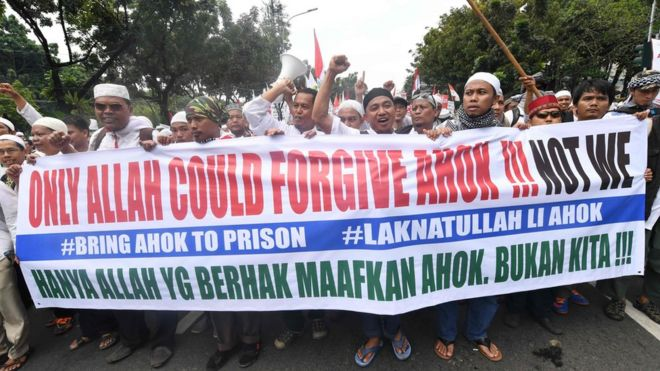 "Protesters carry a banner saying ""only Allah could forgive Ahok!!! Not we"""