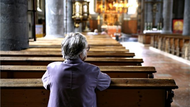 Solitary woman kneeling in church