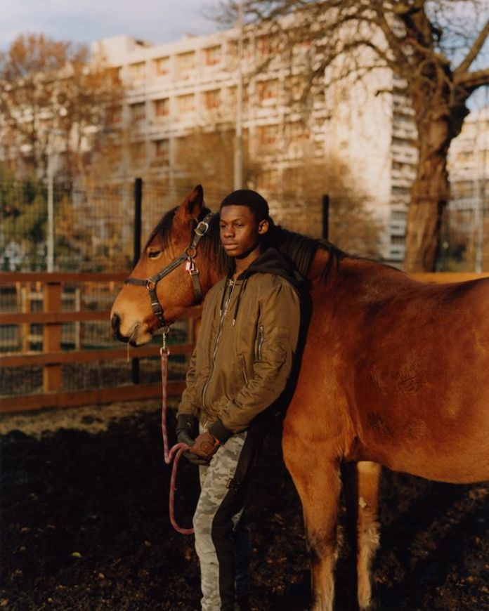 A teenager poses for a portrait with a horse