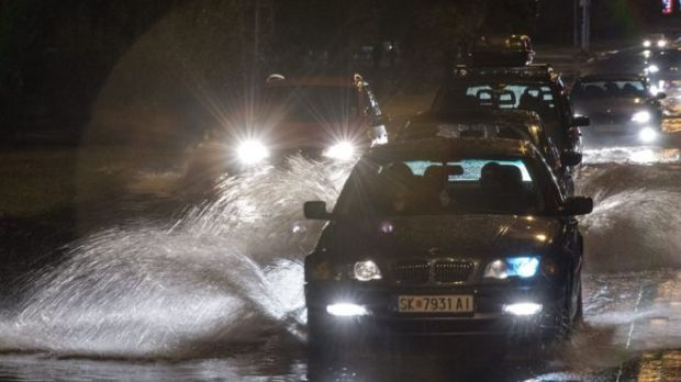 Cars struggling through flooded roads in the dark, 6 August 2015