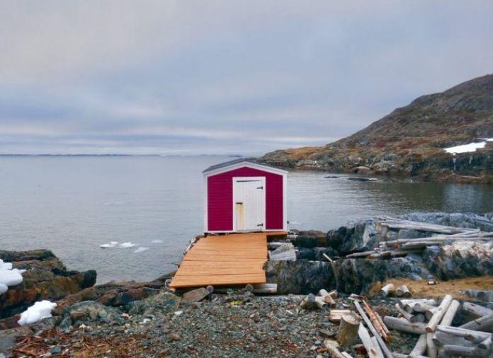 كوخ أحمر صغير على حافة رصيف مائي بالقرب من جزيرة فانكوفر