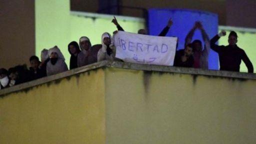 """Internos en la azotea del centro de internamiento de extranjeros en Aluche, Madrid, con una pancarta que reza """"libertad"""""""