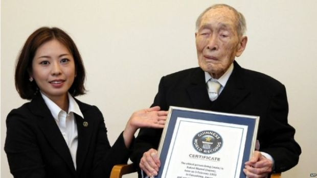 In this file picture taken on 20 August 2014, one-hundred-eleven-year-old Japanese man Sakari Momoi (R) receives a certificate naming him as the world's oldest man by the Guinness World Records at a hospital in Tokyo