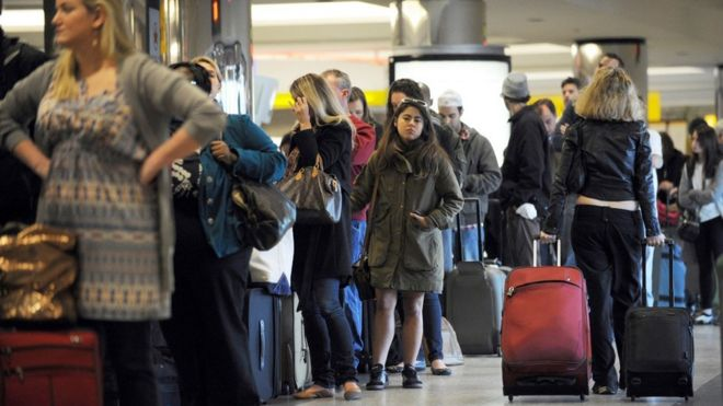 Travellers in a long check-in line at LaGuardia Airport in 2015
