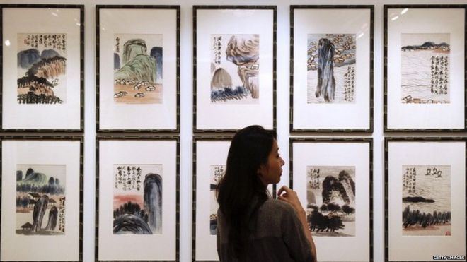 A woman inspects artwork by Chinese artist Qi Baishi entitled 'Landscapes' during a China Guardian auction preview in Hong Kong.