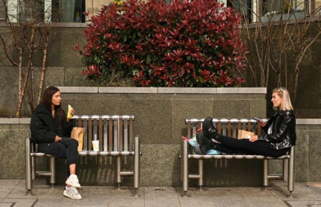 no touch/Two friends enjoy their lunch together at a safe distance in central Leeds on March 21, 2020, a day after the British government said it would help cover the wages of people hit by the coronavirus outbreak as it tightened restrictions to curb the spread of the disease.