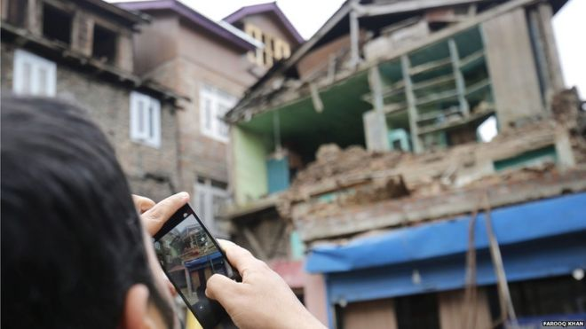A Kashmiri man captures pictures with his mobile phone of a house damaged by an earthquake in Srinagar, Indian Kashmir, 10 April 2016