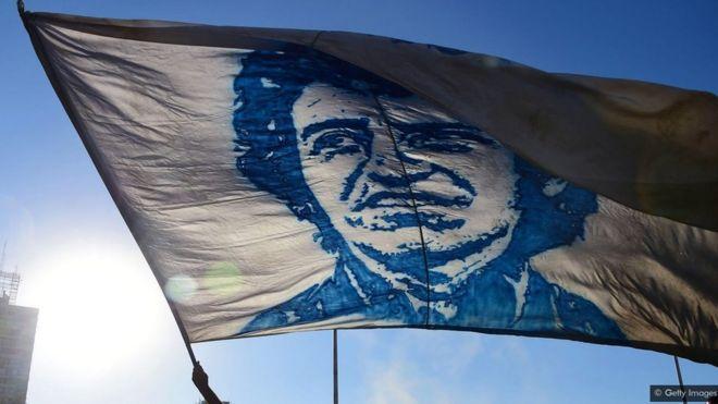علم يحمل صورة المغني التشيلي فيكتور خارا