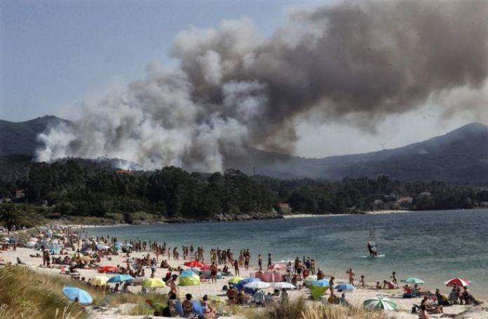 La fumée s'élève d'un feu de forêt près d'une plage touristique