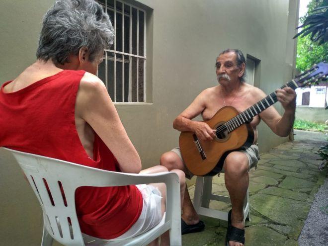 Imagem mostra o músico Lúcio Yanel tocando violão para a mulher, Sueli, que tem Alzheimer