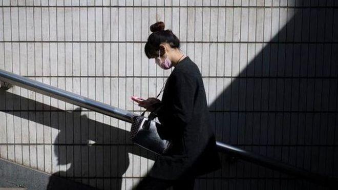 Một phụ nữ đang đọc tin nhắn trên điện thoại