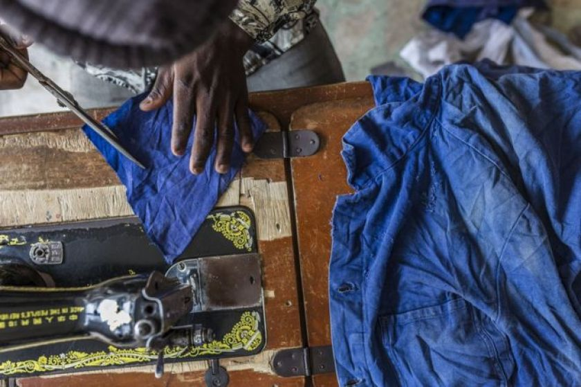 A tailor customises the salvaged clothing.