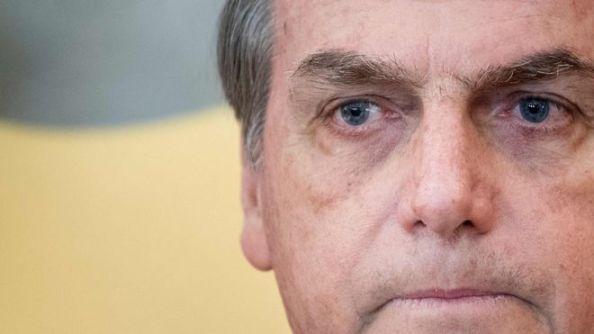 Foto com foco aproximado mostra Bolsonaro olhando para frente com olhar consternado