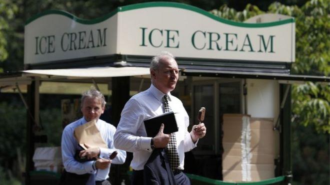Man in suit eating ice cream.