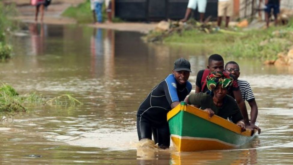 A man ferries residents through a flooded road in the aftermath of Cyclone Kenneth in Pemba, Mozambique, April 29, 2019.