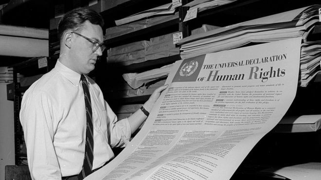 A man looks at one of the first documents published by the United Nations, The Universal Declaration of Human Rights
