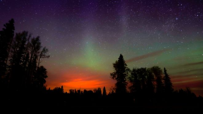 Wildfires glow underneath the Northern Lights, also known as the Aurora Borealis, near Fort McMurray, Alberta (07 May 2016)