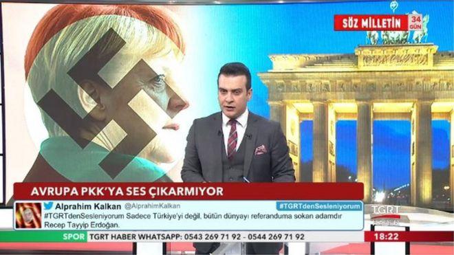 """Screen from Turkish TV station TGRT Haber, showing Angela Merkel with a Nazi swastika superimposed across her face next to Germany's Brandenburg gate. The caption reads """"Europe does not say anything to the PKK"""". the PKK is classified as a terrorist group by Turkey."""