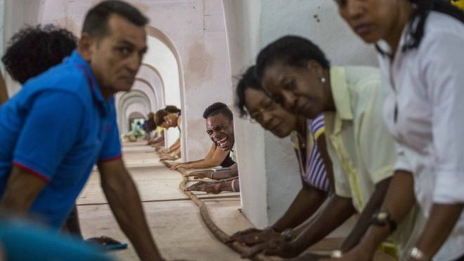 "Dozens of workers help Cuban cigar roller Jose ""Cueto"" Castelar, not pictured, hand roll a 90-meter cigar, in Havana, Cuba, Friday, Aug. 12, 2016"