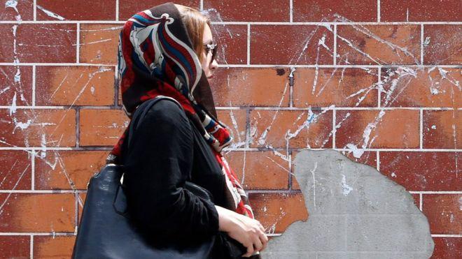 A woman walks down a street in Tehran, Iran (28 April 2016)