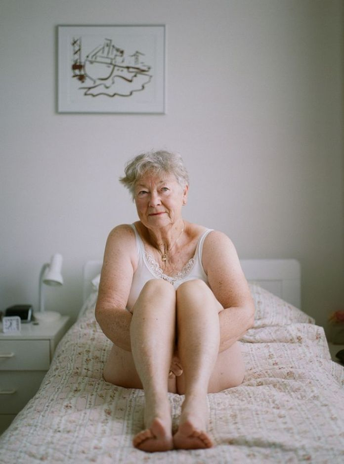 An elderly lady sits on a bed in her underwear